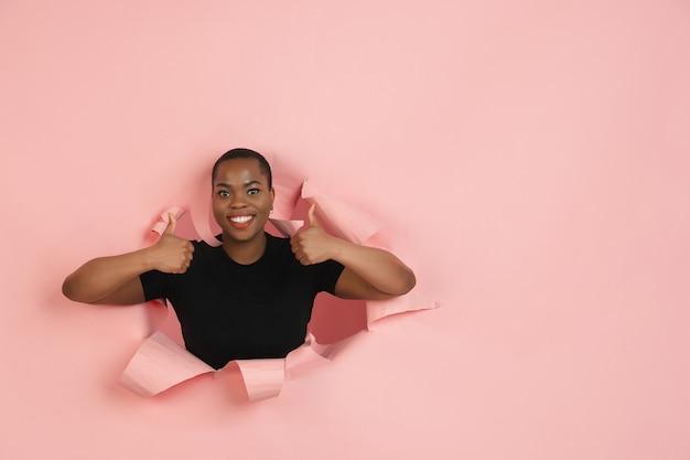 Fröhliche junge frau posiert in zerrissener korallenpapierlochwand emotional und ausdrucksstark
