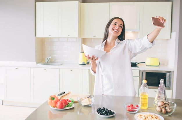 Fröhliche junge frau steht in der küche und hält schüssel mit salat. sie nimmt videos auf und lächelt. mädchen sieht glücklich aus.