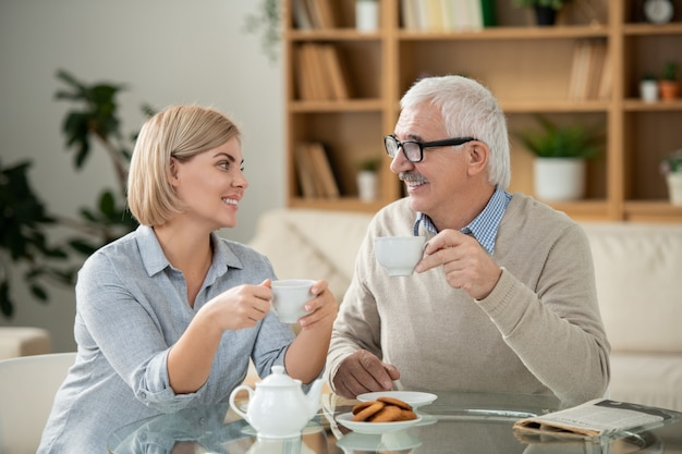 Fröhliche junge frau und ihr älterer vater mit tassen tee, die einander beim sitzen am servierten tisch vor der kamera betrachten