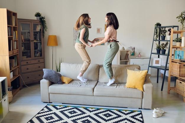 Fröhliche junge frau und ihre tochter im teenageralter mit blonden haaren, die zusammen auf einer großen couch im wohnzimmer springen, während sie sie an den händen hält