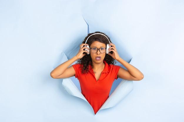 Fröhliche junge frau wirft in zerrissenem blauem papierlochhintergrund auf, emotional und ausdrucksstark