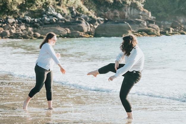 Fröhliche junge frauen, die an einem sommertag am strand lachen und lächeln, urlaub genießen, konzept der freundschaft im freien genießen