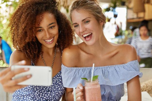 Fröhliche junge frauen oder studentinnen, die gerne für selfies posieren oder videoanrufe auf dem smartphone tätigen, verbringen ihre freizeit nach vorträgen im café. entspanntes lesbisches paar hat im sommer ein gutes resort