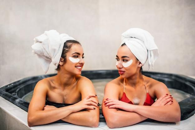 Fröhliche junge frauen schauen sich an und lächeln. sie sitzen im hydromassagebad. frauen haben schönheitsanwendungen. sie tragen bunte badeanzüge und weiße handtücher.