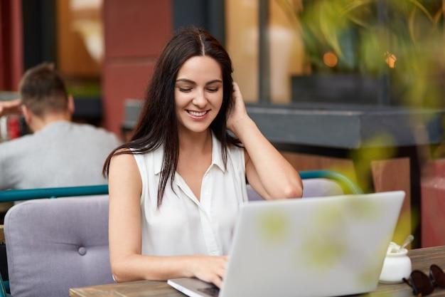 Fröhliche junge freiberuflerin arbeitet am laptop im bistro, hat ein zahniges lächeln als die arbeit endet, gekleidet in weiße bluse