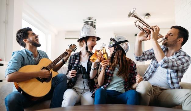 Fröhliche junge freunde, die zusammen feiern und instrumente spielen