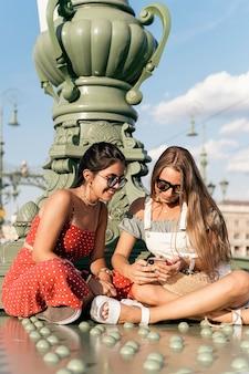 Fröhliche junge freundinnen mit sonnenbrille sitzen in der nähe der säule und surfen im internet auf dem handy der stadtstraße?