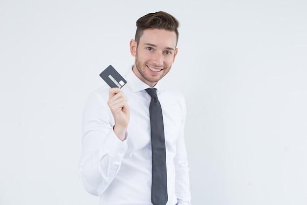 Fröhliche junge führungskraft mit kreditkarte