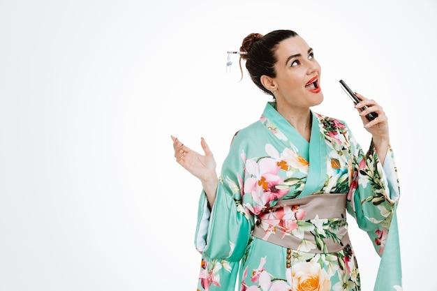 Fröhliche junge geisha-frau im traditionellen japanischen kimono, die ein smartphone hält und es als mikrofon verwendet, um ein lied zu singen, das spaß hat, über der weißen wand zu stehen?