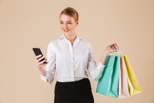 Fröhliche junge geschäftsfrau, die einkaufstaschen unter verwendung des mobiltelefons hält.