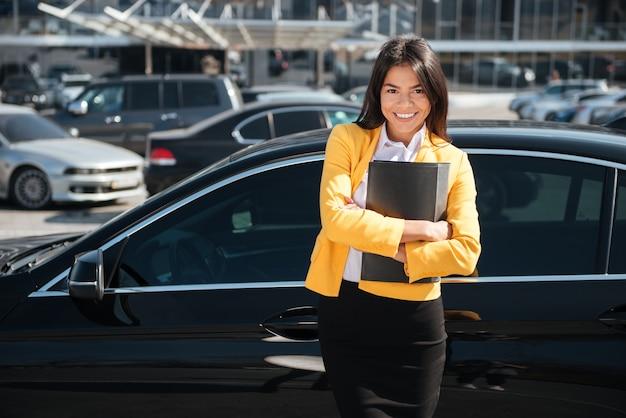 Fröhliche junge geschäftsfrau, die mit verschränkten armen nahe dem auto steht