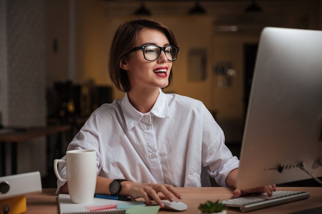 Fröhliche junge geschäftsfrau mit brille, die computer benutzt und im büro lächelt