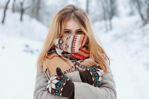 Fröhliche junge glückliche frau mit erstaunlichen braunen augen in einem stilvollen warmen grauen mantel in den vintage-handschuhen im winter-schneepark. fröhliches stilvolles mädchen mit einem wollschal auf ihrem gesicht.