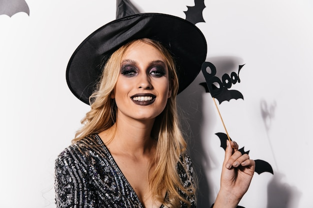 Fröhliche junge hexe. debonair kaukasisches mädchen, das halloween feiert.