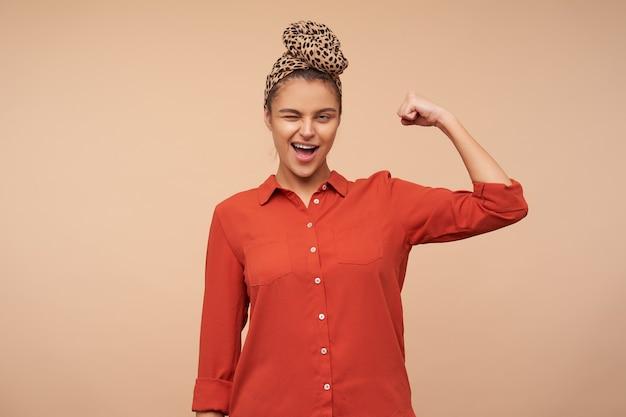 Fröhliche junge hübsche braunhaarige dame mit stirnband zwinkert freudig vorne, während sie ihren starken bizeps mit erhobener hand demonstriert, isoliert über beige wand