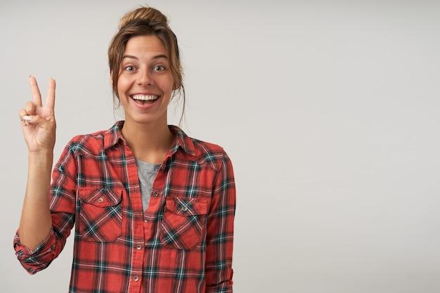 Fröhliche junge hübsche braunhaarige frau mit natürlichem make-up, das siegeszeichen bildet, während sie gern kamera mit breitem lächeln betrachtet, lokalisiert über weißem hintergrund