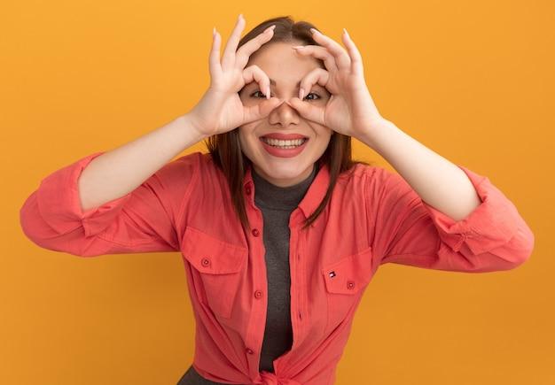 Fröhliche junge hübsche frau, die eine blickgeste macht, die mit den händen als fernglas auf die orangefarbene wand schaut