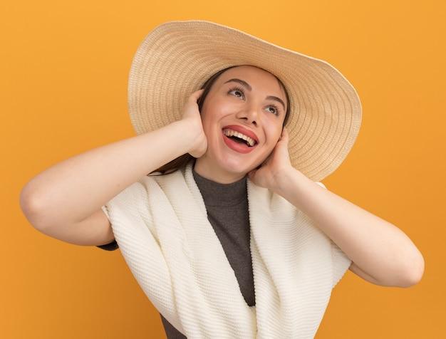 Fröhliche junge hübsche frau mit strandhut, die die hände auf dem gesicht hält und auf der orangefarbenen wand nach oben schaut