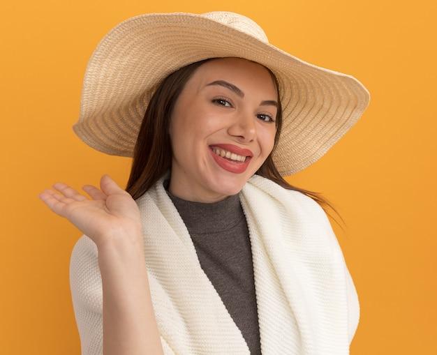 Fröhliche junge hübsche frau mit strandhut, die leere hand isoliert auf orangefarbener wand zeigt