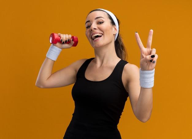 Fröhliche junge hübsche sportliche frau mit stirnband und armbändern, die eine hantel hält und nach vorne schaut und das friedenszeichen isoliert auf der orangefarbenen wand tut