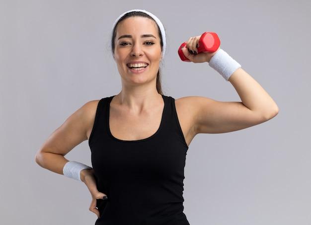 Fröhliche junge hübsche sportliche frau mit stirnband und armbändern, die nach vorne schaut und die hand an der taille hält, die hantel isoliert auf weißer wand hebt