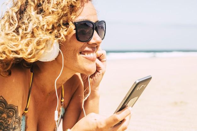 Fröhliche junge kaukasische blonde frau mit sand auf ihren gesichtern am strand, der musik hört