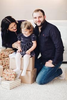 Fröhliche junge kaukasische mama und gutaussehender papa spielt mit ihrem kind in der nähe des weihnachtsbaums