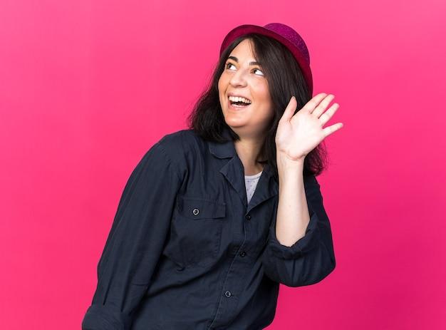 Fröhliche junge kaukasische partyfrau mit partyhut, die aufschaut und dabei hallo geste macht, isoliert auf rosa wand