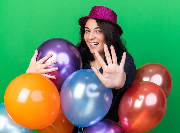 Fröhliche junge kaukasische partyfrau mit partyhut, die hinter ballons steht und sie umarmt und nach vorne schaut, die stop-geste isoliert auf grüner wand macht