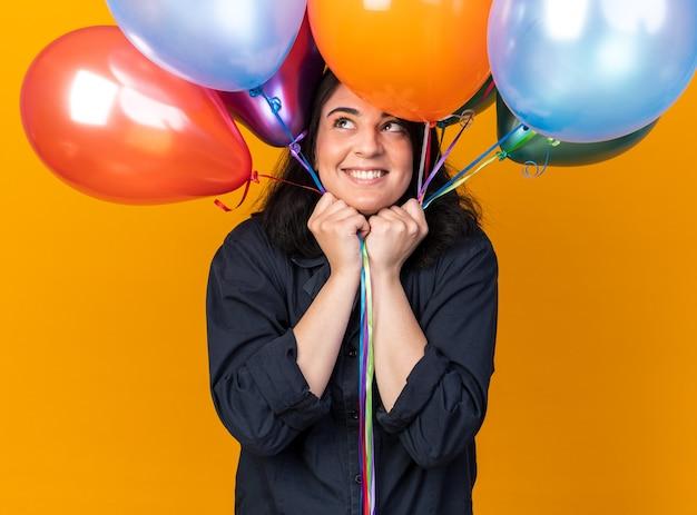 Fröhliche junge kaukasische partyfrau mit partyhut, die luftballons hält und sie einzeln auf oranger wand anschaut