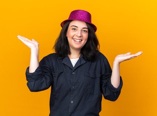Fröhliche junge kaukasische partyfrau mit partyhut, die nach vorne schaut und leere hände isoliert auf oranger wand zeigt