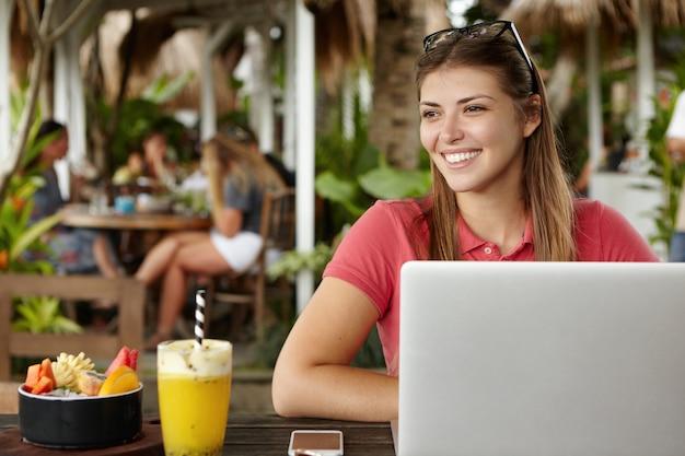 Fröhliche junge kaukasische unternehmerin, die glückliche tage ihres urlaubs genießt, im hotelcafé mit elektronischen geräten und cocktail sitzt und e-mail auf laptop prüft