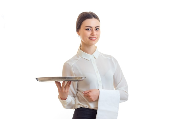Fröhliche junge kellnerin in uniform mit trey in den händen lächelnd isoliert auf weißem hintergrund