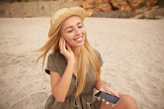 Fröhliche junge langhaarige blonde dame, die ihre augen geschlossen hält, während sie musik hört und glücklich lächelt, musik genießt, während sie über strandhintergrund aufwirft