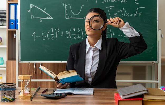Fröhliche junge lehrerin sitzt am tisch mit schulmaterial und schaut mit lupe im klassenzimmer nach vorne