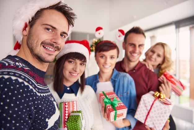 Fröhliche junge leute, die weihnachtsgeschenke halten