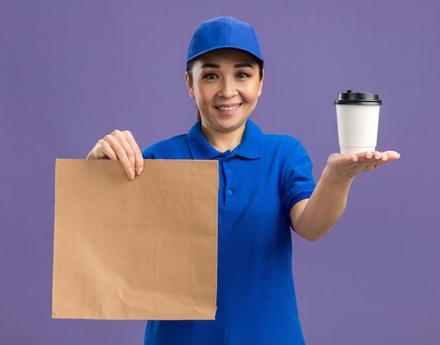Fröhliche junge lieferfrau in blauer uniform und mütze mit papierpaket, die pappbecher mit einem lächeln im gesicht über der lila wand präsentiert