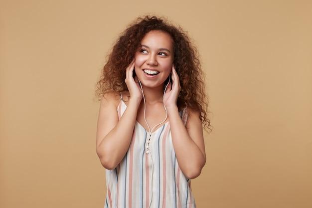 Fröhliche junge lockige brünette frau mit natürlichem make-up, das erhobene hände auf ihren ohrhörern hält, während musik hört, auf beige stehend