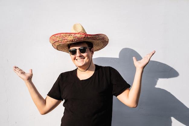 Fröhliche junge männliche person in sombrero. festliches konzept der mexiko-unabhängigkeit des mannes, der nationalen mexikanischen hut trägt