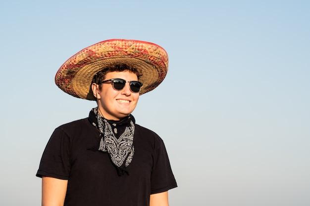 Fröhliche junge männliche person in sombrero im hintergrund des klaren himmels. festliches konzept der mexiko-unabhängigkeit des mannes, der nationalen mexikanischen hut und bandana des westlichen stils trägt