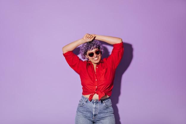 Fröhliche junge moderne frau im roten hemd mit langen ärmeln und gläsern in form von herzen, die auf purpur aufwerfen.