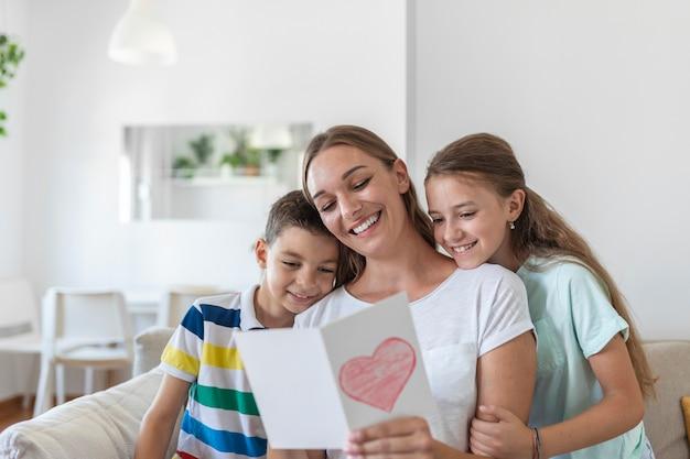 Fröhliche junge mutter und kleine kinder sitzen auf dem sofa und umarmen sich beim lesen von wünschen und glückwünschen mit urlaub in einer präsentierten postkarte zu hause
