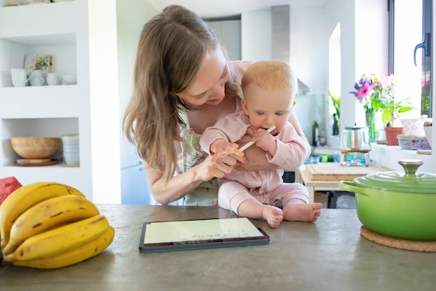 Fröhliche junge mutter und kleine tochter kochen zusammen zu hause, beobachten rezepte auf block, mit tablette. kinderbetreuung oder kochen zu hause konzept