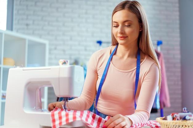 Fröhliche junge näherin, die am arbeitstisch in ihrem büro sitzt