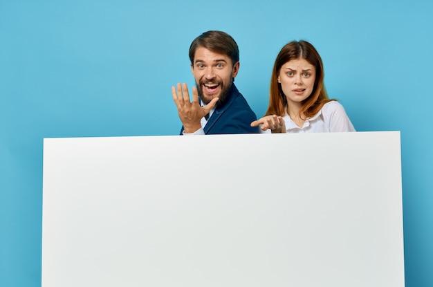 Fröhliche junge paarbeamte präsentieren weißbuchwerbung