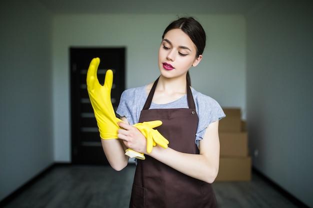 Fröhliche junge putzfrau zieht gummihandschuhe an und macht sich bereit für den frühjahrsputz