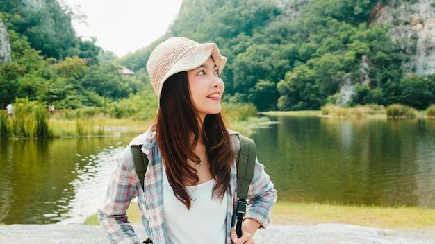 Fröhliche junge reisende asiatische dame mit rucksack, der am bergsee geht. koreanisches jugendlich mädchen genießen ihr urlaubsabenteuer, das glückliche freiheit fühlt. lifestyle reisen und im freizeitkonzept entspannen.
