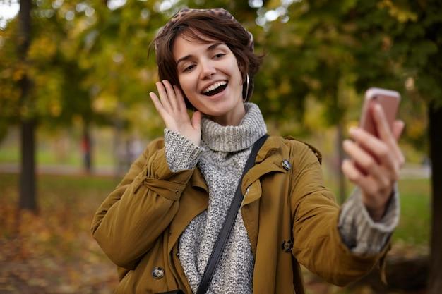 Fröhliche junge reizende braunhaarige frau mit lässiger frisur, die hand mit handy anhebt, während foto von sich selbst macht, breit lächelnd, während über vergilbten bäumen posiert