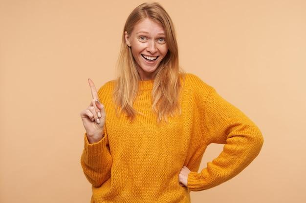 Fröhliche junge reizende langhaarige rothaarige frau mit lässiger frisur, die ihren zeigefinger angehoben hält, während sie glücklich mit breitem lächeln schaut und auf beige posiert