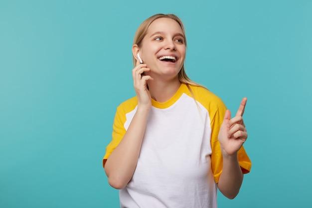 Fröhliche junge reizende weißköpfige dame mit lässiger frisur, die ohrhörer trägt und gerne mit breitem lächeln beiseite schaut, gekleidet in weiß und gelb, während sie auf blau posiert